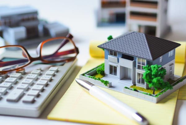 住宅模型と電卓とペン