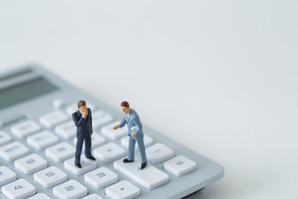 電卓とビジネスマンのミニチュア