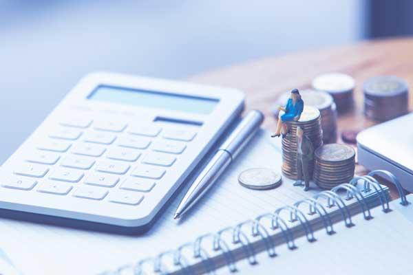 ワンルームマンション売却の税金と確定申告 電卓と積み上げたコインに乗るビジネスマンのミニチュア模型