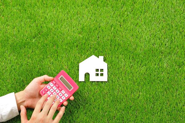 田舎の土地を売るための8つのコツ 芝生の上の電卓と家模型